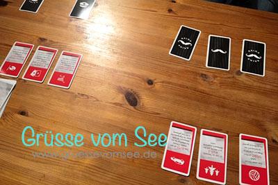 Dieses Bild zeigt eine Spielsituation. Beide Spieler haben ein Codewort verdeckt vor sich hingelegt und ihre Themenkarten offen auf dem Tisch.